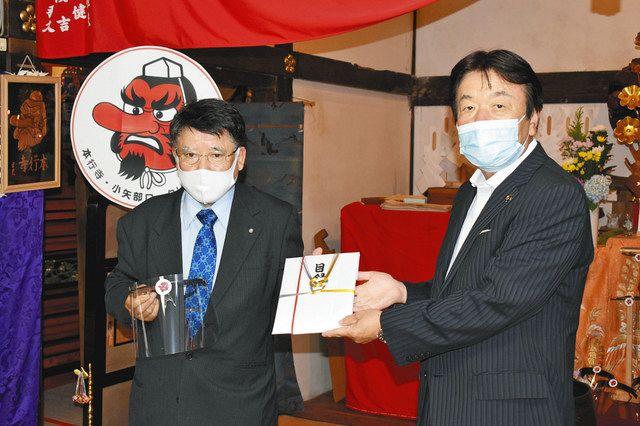 桜井森夫市長(右)に目録とフェースガードを手渡す中橋勉会長=小矢部市の本行寺で